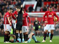 Ander Herrera of Manchester United protests to referee Mark Clattenburg (2nd R) after his red card