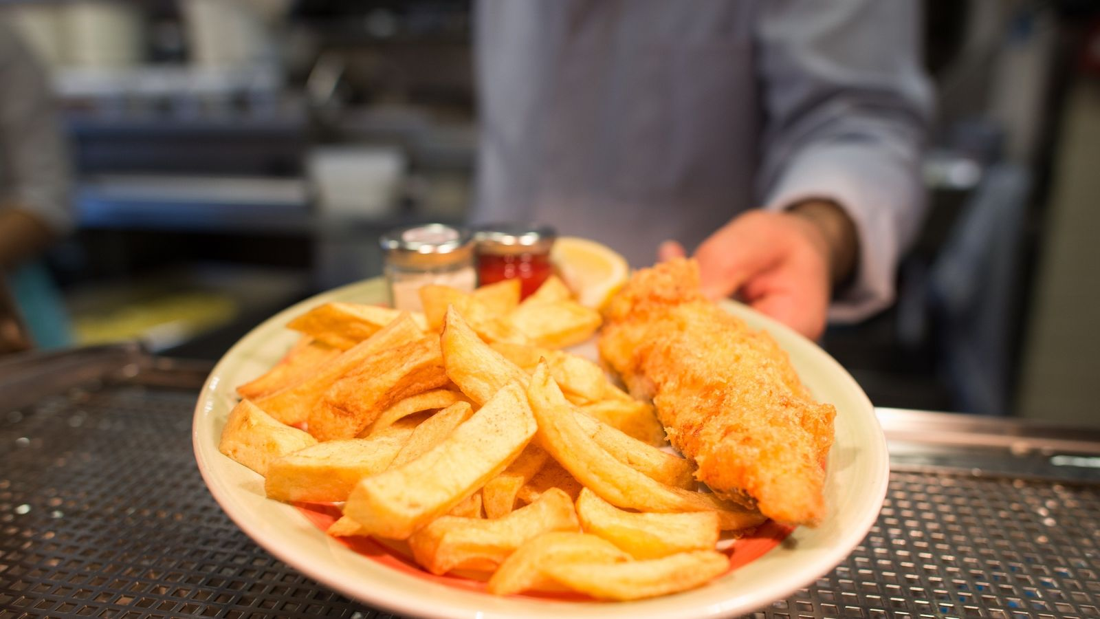 A chef poses with a plate of fish and chips at Poppies fish and chip restaurant in east London on January 26, 2015. Fish and chips, that a classic British dish, is a popular takeaway food in the UK with local media reporting that somewhere in the region of 250 million portions are served up annually