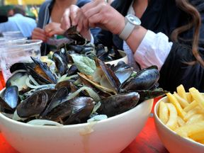 A person eats mussels and French fries