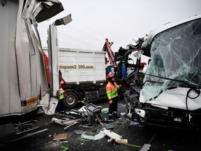 A firefighter inspects the front of a bus involved in a multiple vehicle pile-up on the A13 in France