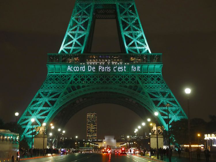 The Eiffel Tower (Tour Eiffel) is illuminated with the lettering reading 'The Paris accord is done' in Paris on November 4, 2016, to celebrate the first day of the application of the Paris COP21 climate accord
