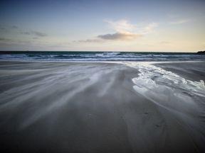 Strong off shore winds blow as waves break on the beach in Sandfly Bay near Dunedin, on September 21, 2011