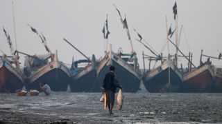 A Rohingya fisherman walks on the beach in Sittwe in the state of Rakhine, Myanmar