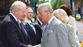 The Prince of Wales shakes hands with Northern Ireland's Deputy First Minister Martin McGuinness outside St Patrick's Church in Belfast, 2015