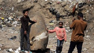 Matariya residents rest against what appears to be the head of an unearthed statue that workers say may depict Pharaoh Ramses II, in Cairo, Egypt