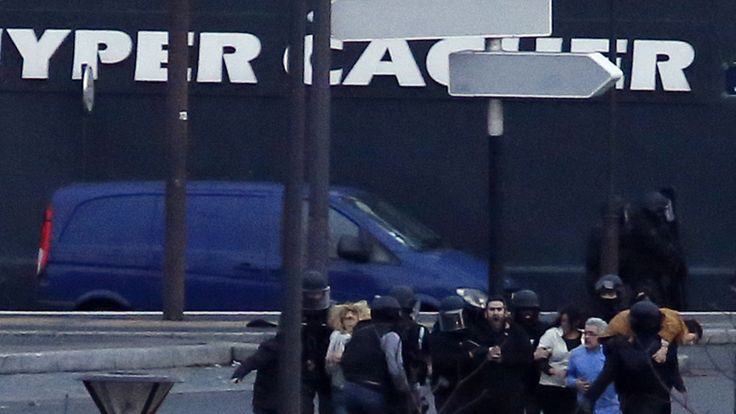 Hostages are escorted out of a kosher grocery store in Porte de Vincennes