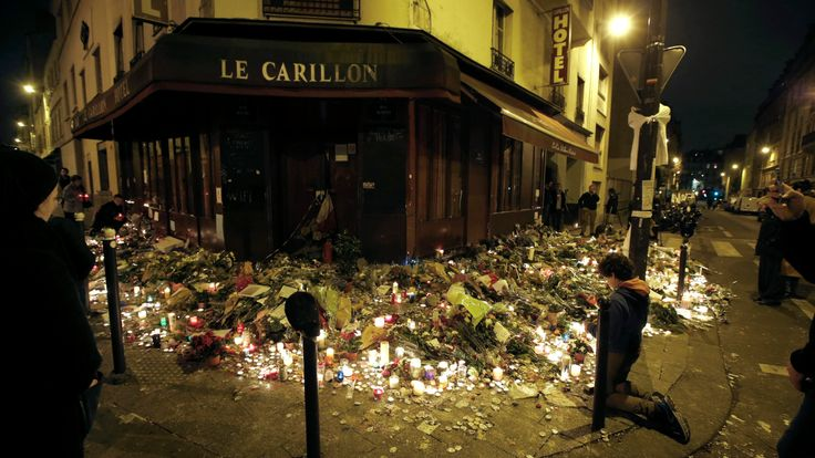 People pray outside Le Carillon restaurant, one of the attack sites in Paris