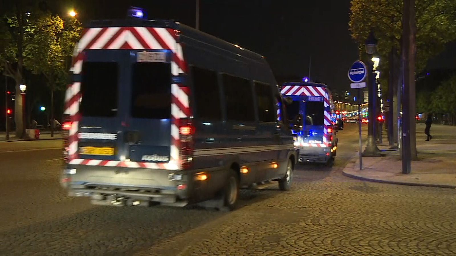 French police vehicles drive in convoy through Paris streets after shooting incident