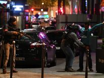 Police officers searching a man on the Champs-Elysees