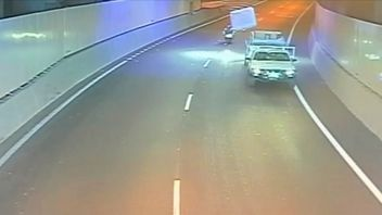 A mattress flies on the back of a truck and hits a motorcyclist
