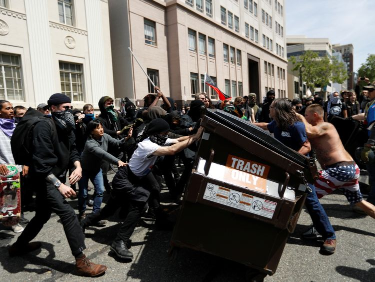 Demonstrators for (right) and against (left) Donald Trump push a garbage container toward each