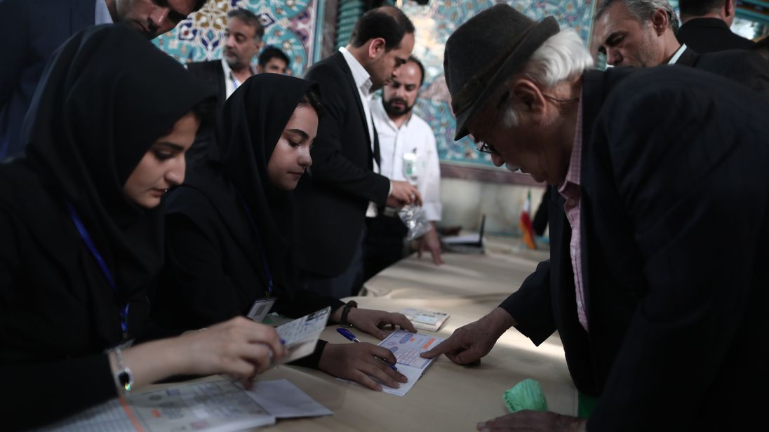 An elderly man registers to cast his ballot at a polling station in Tehran on May 19, 2017