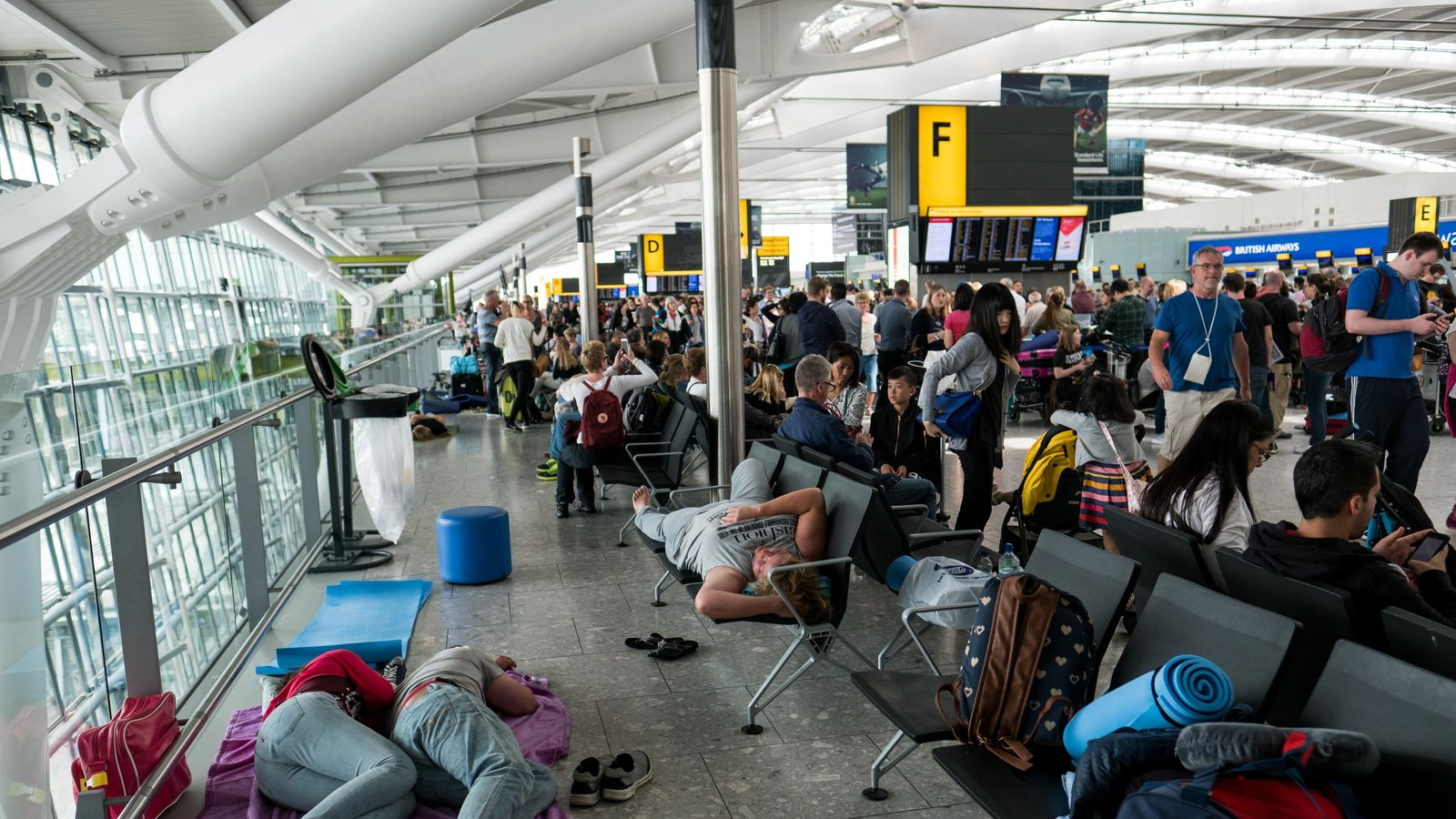 People sleep at Heathrow Airport as a British Airways IT chaos affected 75,000 flights
