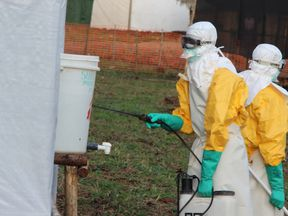 Hygienists wearing protective suits disinfect the toilets of the Ebola treatment centre in Lokolia, on October 5, 2014
