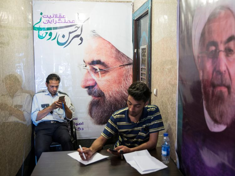 Men use their smartphones to follow election news as posters of Iran's President Hassan Rouhani are seen in Tehran, Iran May 17, 2017