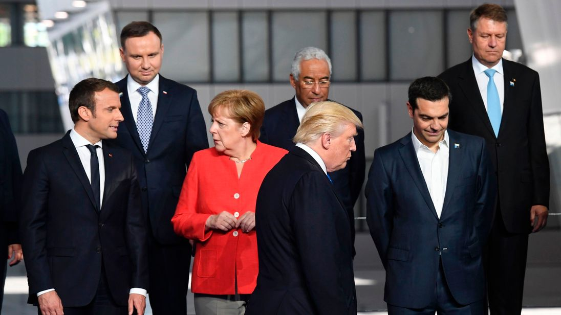 French President Emmanuel Macron (L) and German Chancellor Angela Merkel (2nd L) speaks as US President Donald Trump (C)
