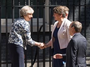 Theresa May and Arlene Foster shake hands shortly before striking a deal