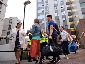 "Residents leave a tower block on the Chalcots Estate in Camden, London, as the building is evacuated in the wake of the Grenfell Tower fire to allow ""urgent fire safety works"" to take place."