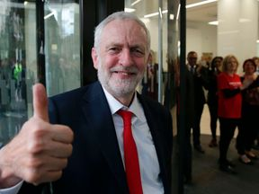 Jeremy Corbyn gives a thumbs up as he arrives at Labour HQ