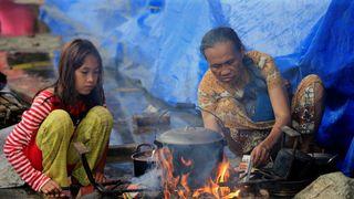 Evacuees cook food in a open area of the evacuation centre at Saguiran village in Lanao Del Sur