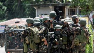 Soldiers manoeuvre through a street in Marawi