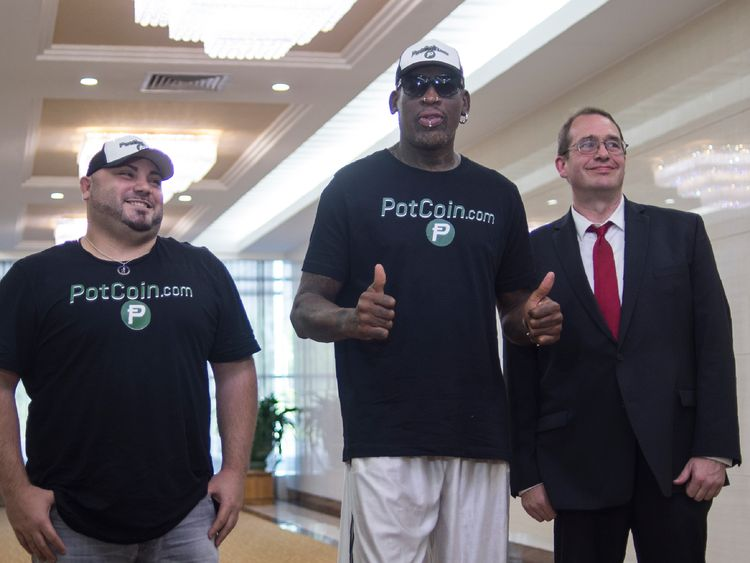 Flamboyant former NBA star Dennis Rodman (C) of the US poses with members of his party following his arrival at Pyongyang International Airport