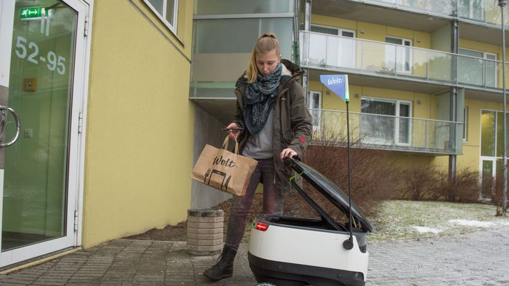 A woman takes delivery of food from a six-wheeled robot by Starship Technologies from restaurant in Tallinn, Estonia on February 16, 2017