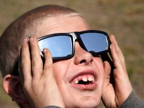 A young boy tries out his new solar glasses in Guernsey, Wyoming