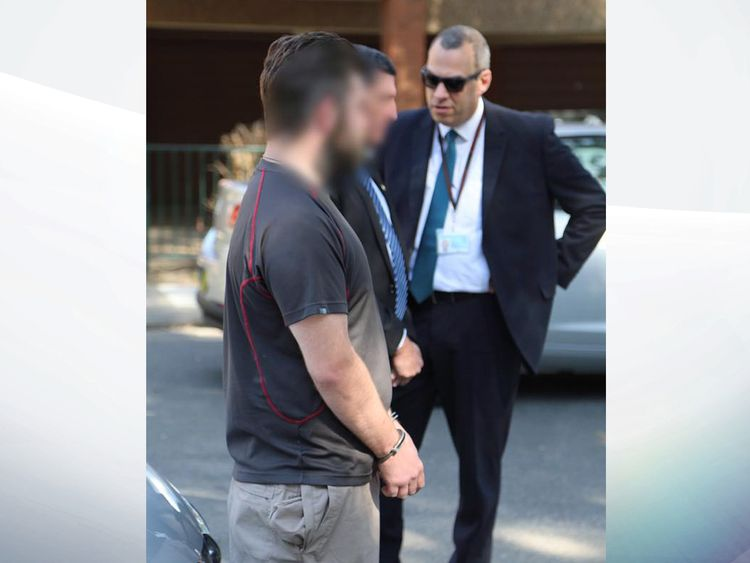 Police stand with the British man after he is arrested in Sydney. Pic: NSW Police