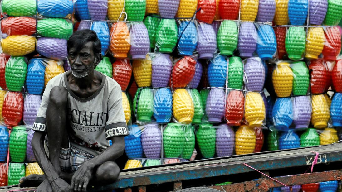 A man rests on his cart after unloading plastic jugs near a shop at a main market in Colombo, Sri Lanka