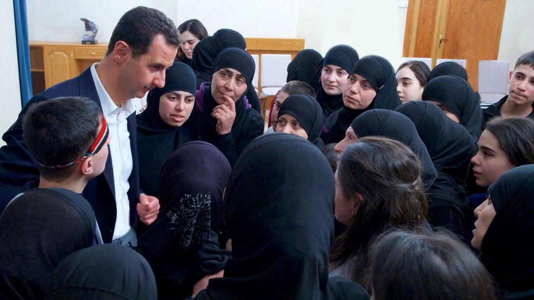 Mr Assad with women and children which he claims were freed after being held by opposition forces for more than three years