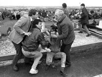 McGuinness assists an injured man at Milltown Cemetary, Belfast, after an attack at the funerals of three IRA members killed in Gibraltar, 1988