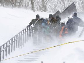 Japan Self-Defense Forces soldiers carry victims after an avalanche hit a group of high school students and teachers climbing near a ski resort in Nasu town, north of Tokyo, Japan. Pic: Kyodo via Reuters