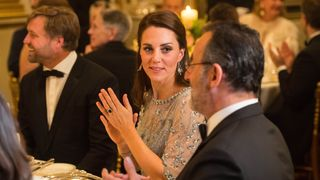 The Duchess of Cambridge speaks with French actor Jean Reno during the dinner