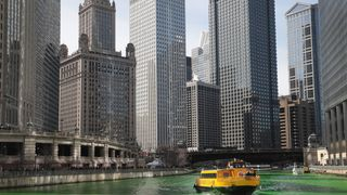 A water taxi navigates the Chicago River shortly after it was dyed green in celebration of St. Patrick's Day in Chicago, Illinois