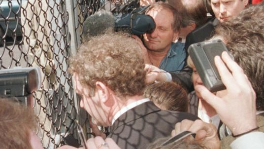 Chief Negotiator for Sinn Fein Martin McGuinness shut out from the Ulster talks at Stormont speaks to the media through a fence, 1996