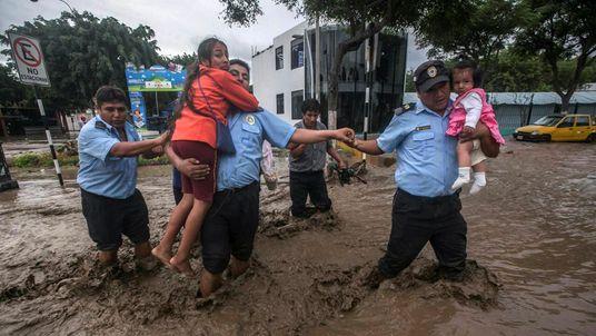 Municipality guards help residents cross a flooded street in Trujillo, northern Peru