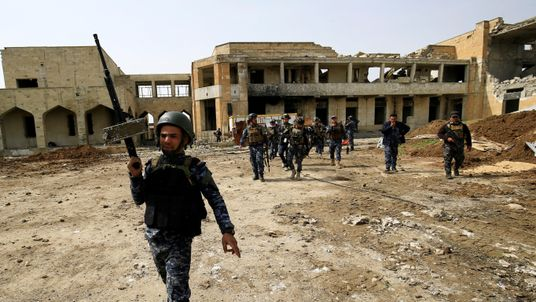 RTX31PPC19 Mar. 2017Mosul, IraqFederal police officers carry their weapons as they attempt to break into the Old City during a battle against Islamic State militants, in Mosul, Iraq March 19, 2017. REUTERS/Thaier Al-Sudani