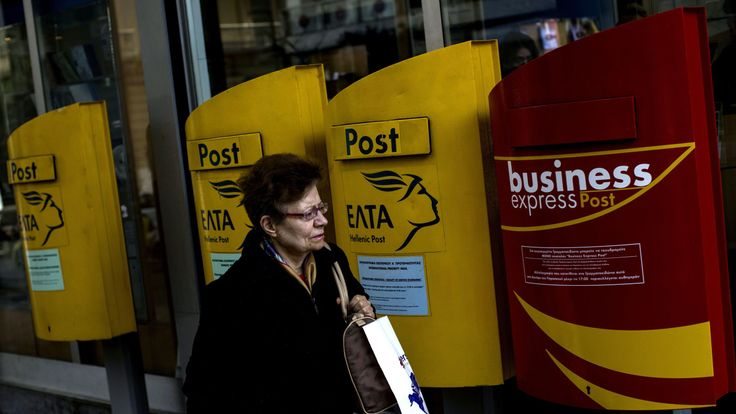 A woman walks past mailboxes outside a post office on March 17, 2017 in the Greek capital, Athens, a day after a mail bomb, posted from Greece, exploded at the International Monetary Fund (IMF) offices in Paris