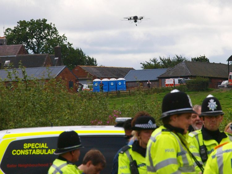 A police drone flies over a line of officers blocking protesters in Derbyshire