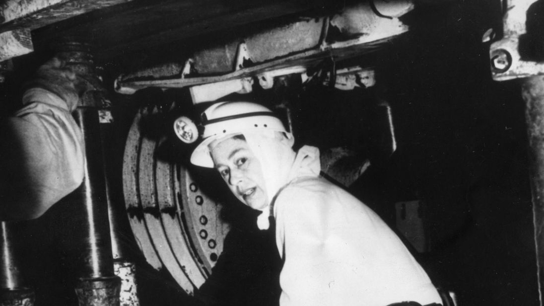 Queen Elizabeth II stoops to enter the coalface - 600 yards underground - during a visit to the Silverwood Colliery near Rotherham