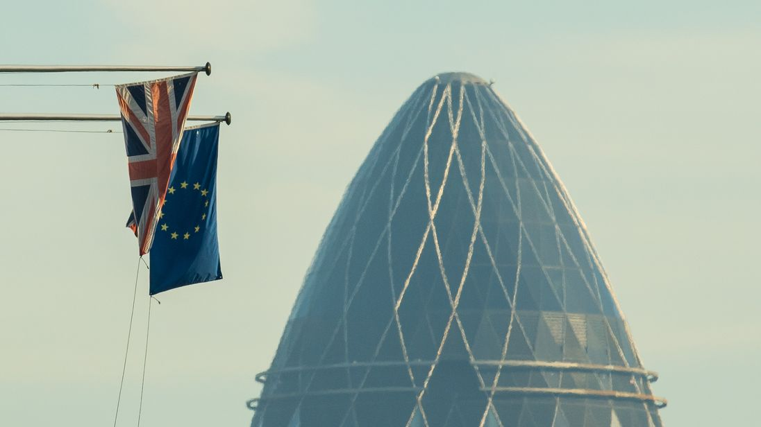 A Union Flag and a European Union flag seen alongside 30 St Mary Axe, also known as the Gherkin, in the City financial district of central London