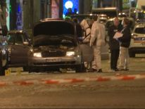 Forensics officers search a car on the Champs-Elysees
