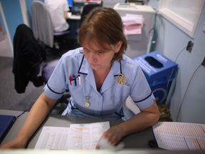 A nurse writes up her case notes at a work station in the recently opened Birmingham Queen Elizabeth Hospital on February 7, 2011