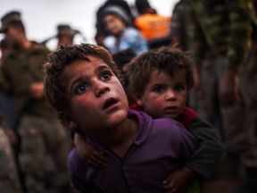 Syrian Kurdish children arrive at the border between Syria and Turkey after several mortars hit both side in the southeastern town of Suruc, in the Sanliurfa province on September 29, 2014