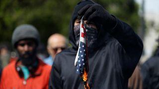 An anti-Trump protester burns an American flag