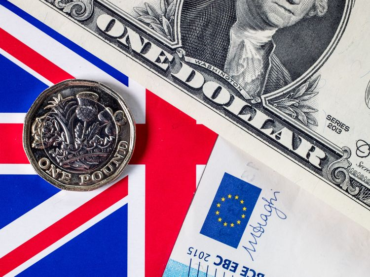 The new £1 pound coin is seen alongside US dollar bills and euro notes on April 4, 2017 in Bath, England
