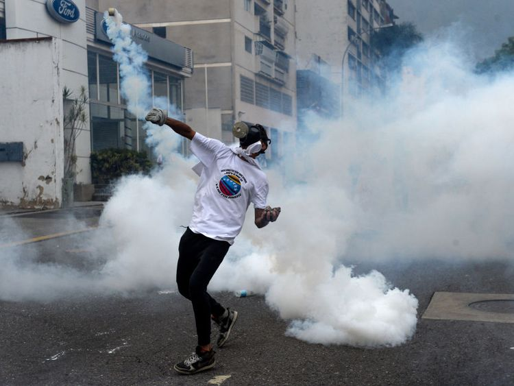 A demonstrator throws a tear gas grenade back at police during a march against Mr Maduro