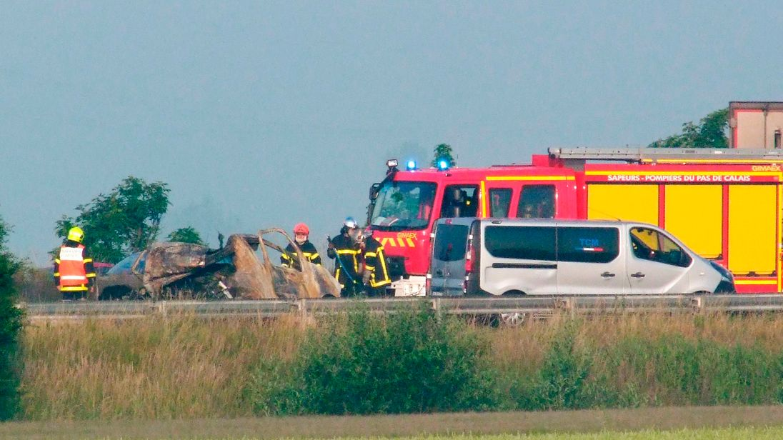 Firefighters and rescuers stand next to the wreckage of a van