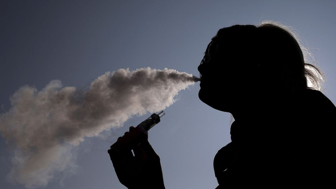 A woman exhales vapour from an e-cigarette
